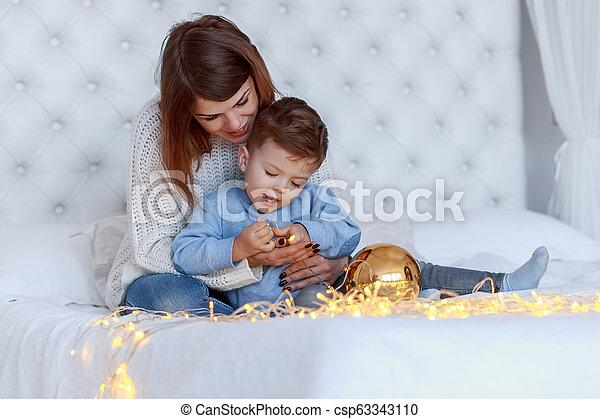 Un chico con su madre frente al árbol de Navidad. Felicidad y un gran concepto familiar - csp63343110