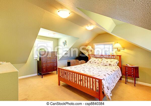 El dormitorio del ático con paredes verdes y cama grande. - csp8840384