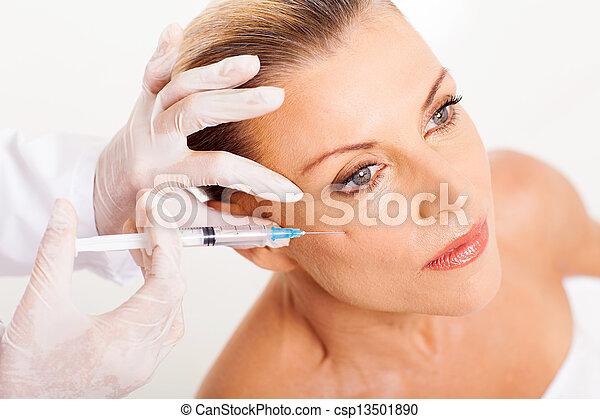 Der Arzt, der Frauen mittleren Alters mit einer Spritze versorgt - csp13501890