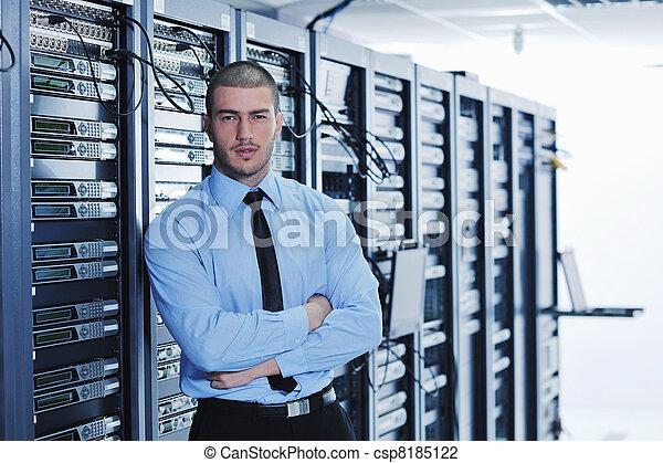 Joven ingeniero en la sala de servidores del centro de datos - csp8185122