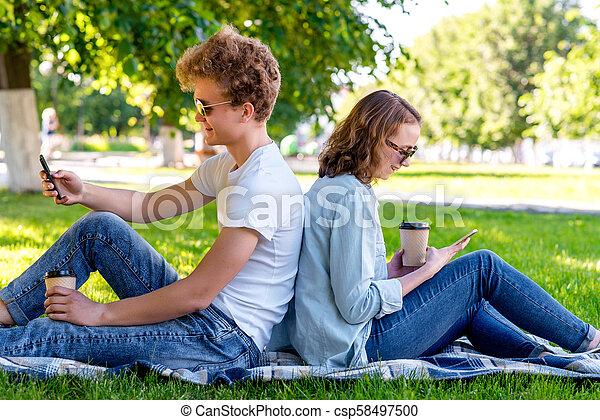 été, il, sien, hands., institute., étudiants, thé, tient, école, repos, correspondre, girl., park., regarde, social, networks., type, a, smartphone., après - csp58497500