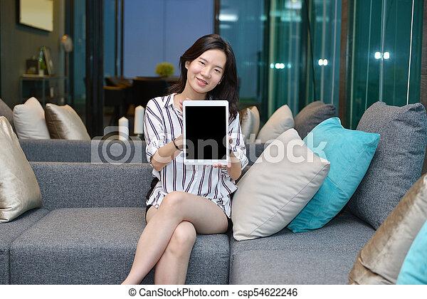 żyjący, kobieta, tabliczka, handlowy, sofa, pokaz, przypadkowy, asian, okienko osłaniają, pokój - csp54622246