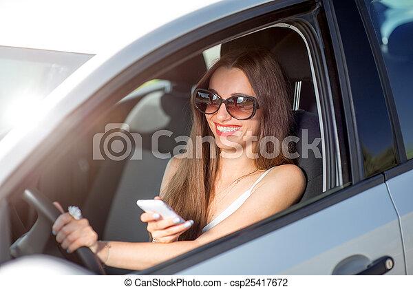 γυναίκα , αυτήν , οδήγηση , αυτοκίνητο , νέος , τηλέφωνο , χρόνος , χρησιμοποιώνταs , χαμογελαστά  - csp25417672