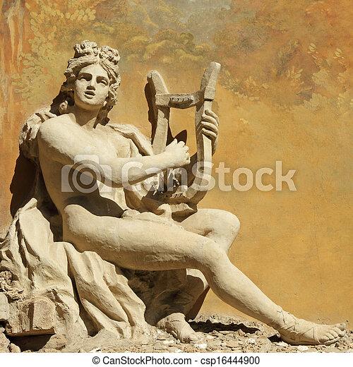 Un antiguo dios con el instrumento principal, tallado decorativo en la pared - csp16444900