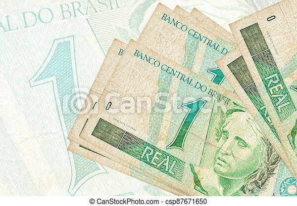 1 Brazilian real bills lies in stack on background of big semi-transparent banknote. Abstract presentation of national currency - csp87671650