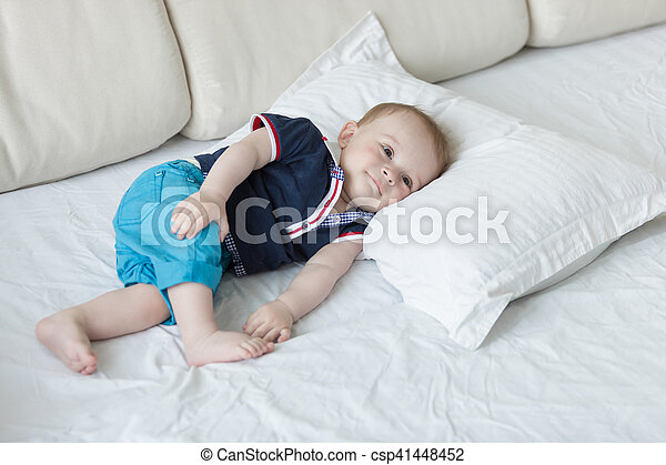 1 year old baby boy lying on big pillow on bed - csp41448452