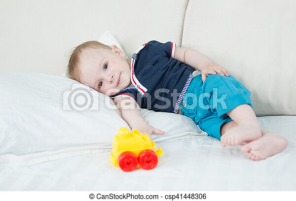 Cute 1 Year Old Baby Boy Resting On Bed After Playing With Toys