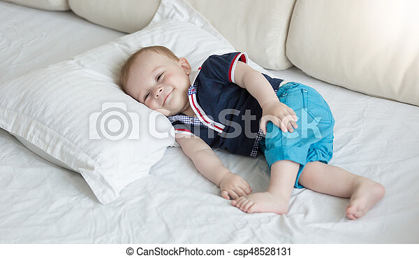 1 year old baby lying on big pillow on bed - csp48528131