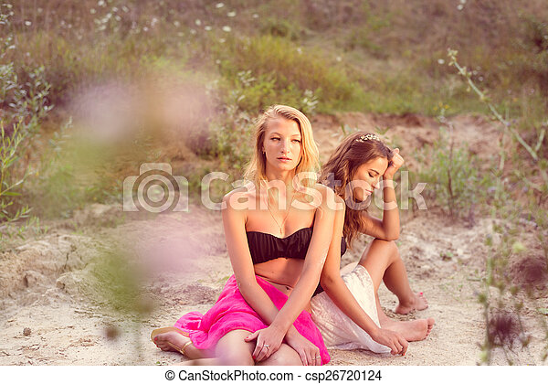 2 sad beautiful brunette and blonde young women best friends with bare shoulders in silk pink skirts sitting back to back on sandy cracked ground outdoors copyspace background - csp26720124
