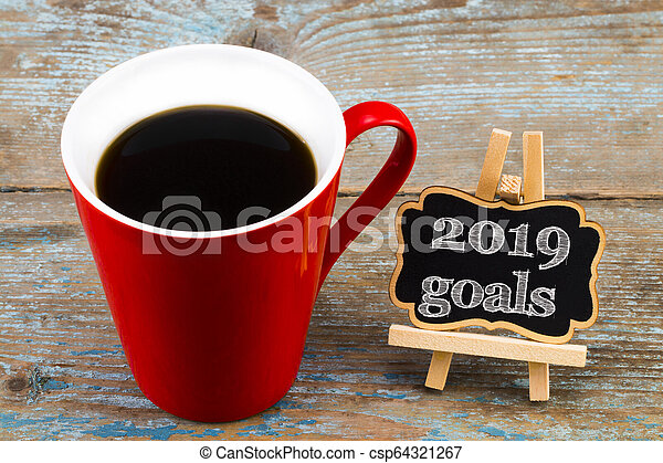 2019 goals on blackboard with a cup of coffee, on wooden background. New Year resolutions concept - csp64321267