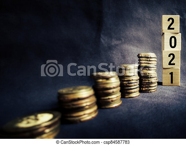2021 number written on wooden blocks with stacks of coins background. Business concept. Stock photo. - csp84587783