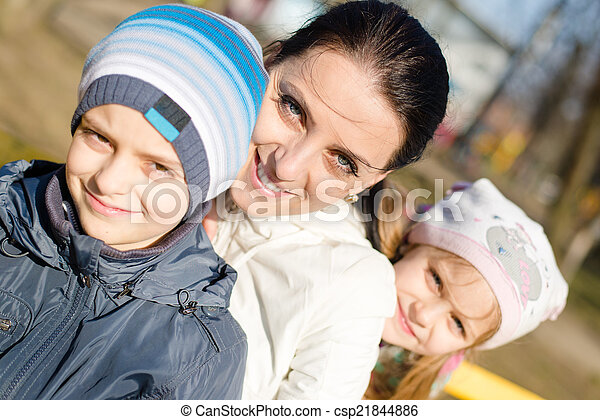3 people beautiful young mother with two children, son and daughter having fun happy smiling & looking at camera, closeup portrait on spring or autumn outdoors background - csp21844886
