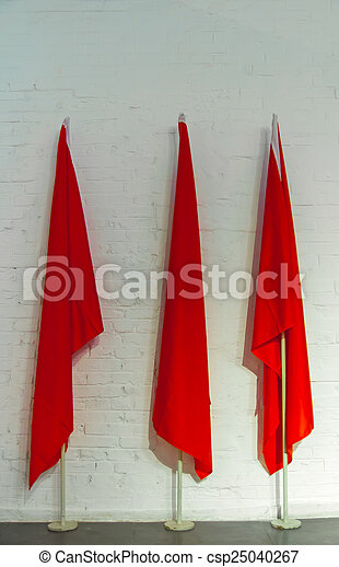 3 red flags on white brick wall - csp25040267