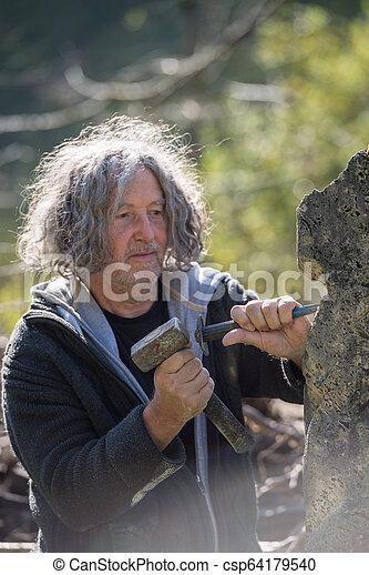 Escultor bohemio senior tallando piedra - csp64179540