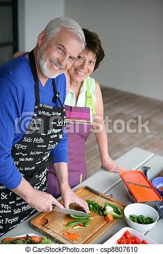 Una pareja mayor cocinando - csp8807610