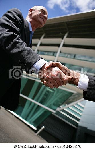 Hombres de negocios mayores estrechando la mano - csp10428276