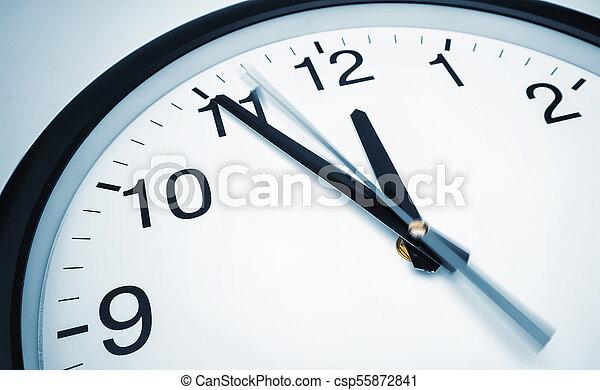 5 min before 12 o clock on a wall clock closeup shot of a classic