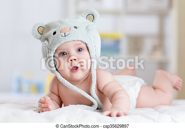 5 months baby girl weared in funny hat lying down on a blanket - csp35629897