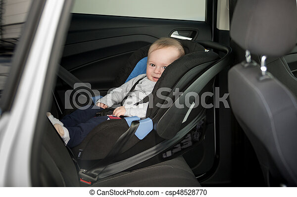 6 Months Old Baby Boy Sitting In Child Seat At Car