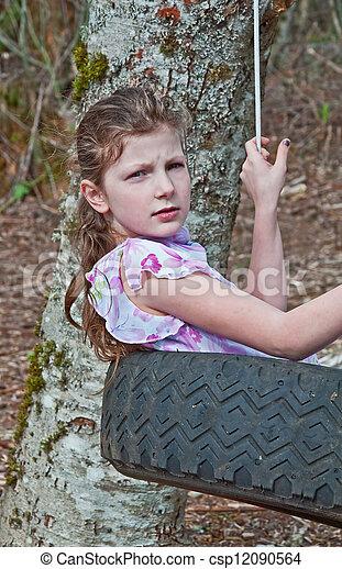 9 Year Old Caucasian Girl in Tire Swing - csp12090564