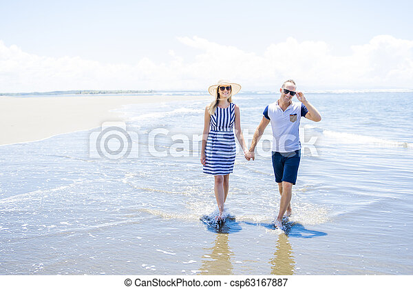 A beautiful and happy couple having fun at the beach of Costa Rica - csp63167887