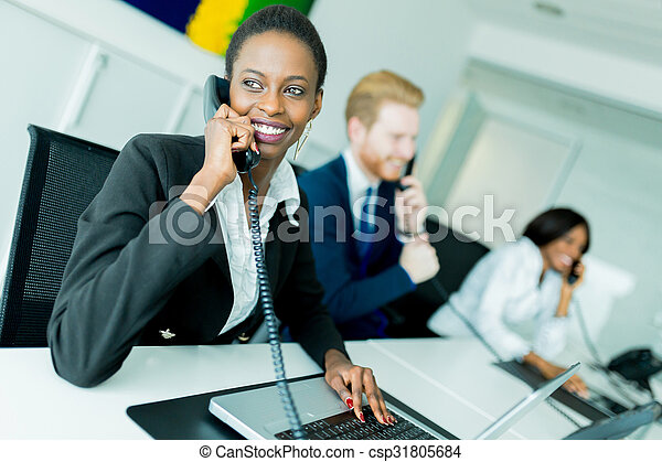 A beautiful, black, young woman working at a call center in an office with her red haird partner on the other end of the desk - csp31805684