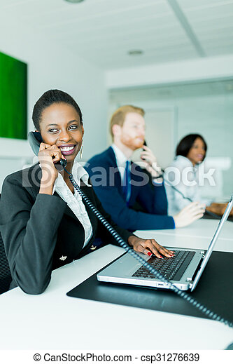 A beautiful, black, young woman working at a call center in an office with her red haird partner on the other end of the desk - csp31276639