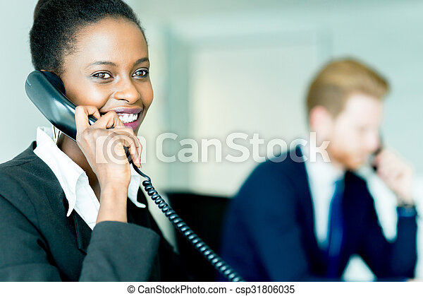 A beautiful, black, young woman working at a call center in an office with her red haird partner on the other end of the desk - csp31806035