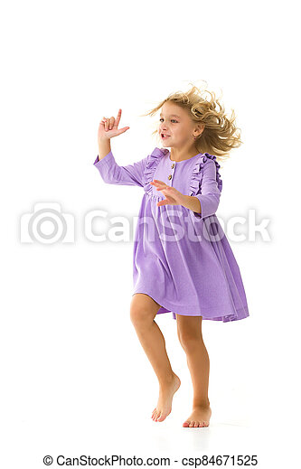 A beautiful little girl stands in the wind, her hair and clothes are developing greatly. The concept of style and fashion. - csp84671525