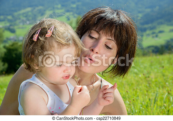 a beautiful mom and daughter play with a flower in nature - csp22710849