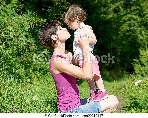 a beautiful mom is a hug to her daughter in nature - csp22710417