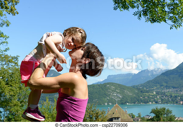 a beautiful mom is a hug to her daughter in nature - csp22709306