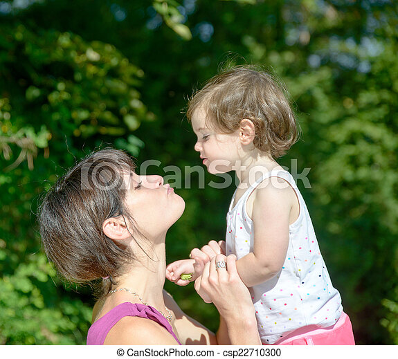 a beautiful mom is a hug to her daughter in nature - csp22710300