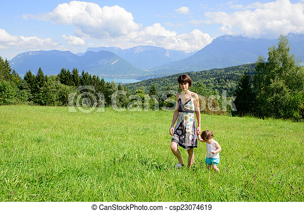 a beautiful mother and daughter walking in the mountains - csp23074619