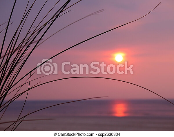 A beautiful sunset over the ocean with dune grass in the foreground. - csp2638384