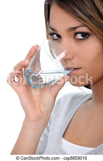 A beautiful woman drinking a glass of water. - csp8859016