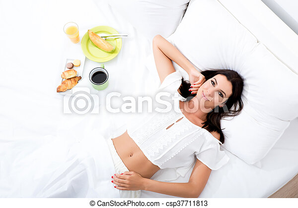 A beautiful young woman having breakfast in bed - csp37711813