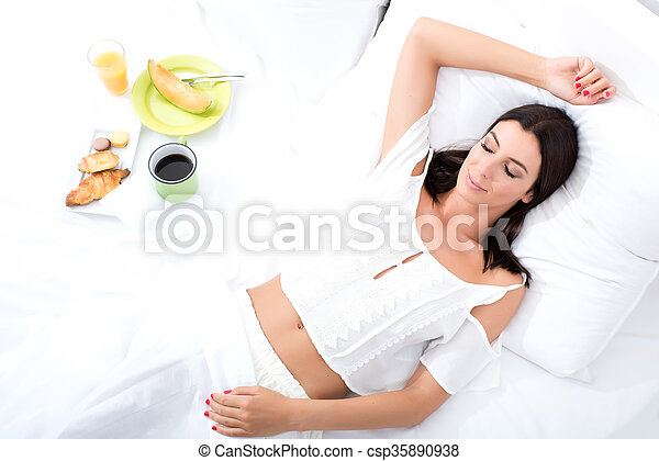 A beautiful young woman having breakfast in bed - csp35890938