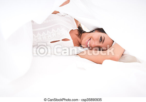 A beautiful young woman under the sheets in the bed - csp35890935