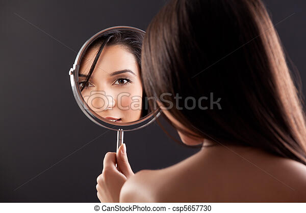 a beauty image of a young woman looking into a mirror, smiling. - csp5657730