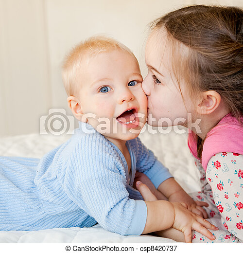 A big sister kisses her little brother - csp8420737