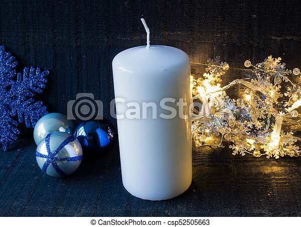 a big white candle with christmas decorations and garland on the wooden blue surface csp52505663
