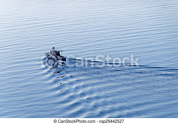 A blue fishing boat travelling out on the sea - csp29442527