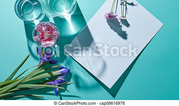 A Bouquet Of Flowers With Vases And A White Sheet Of Paper On A Blue