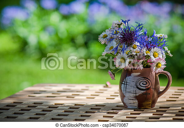 A bouquet of wildflowers in a circle on the table - csp34070087