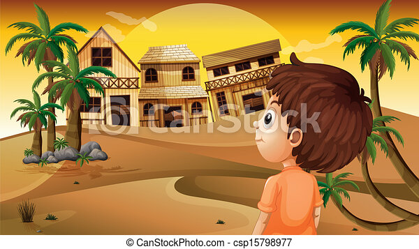 A boy at the desert standing in front of the wooden houses - csp15798977