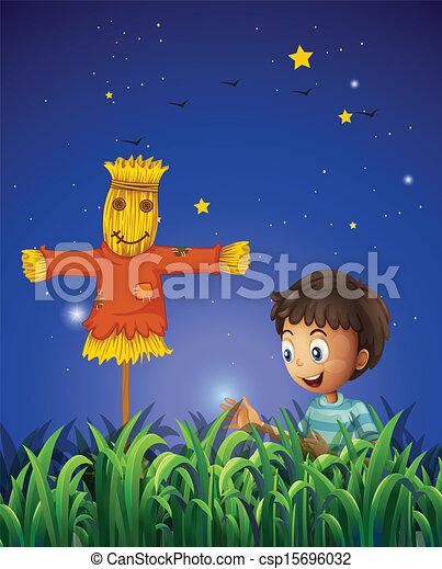 A boy at the farm with a scarecrow - csp15696032