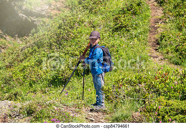 A boy traveler is standing on the path to the top of the mountain range - csp84794661