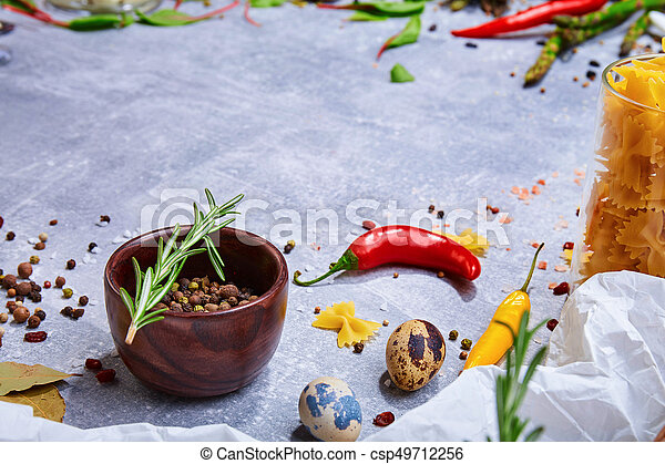 A brown wooden bowl with colorful seasoning on a gray background. Spices with hot colorful pepper, bay leaves and a rosemary twig. - csp49712256