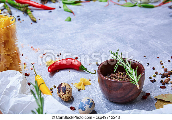 A brown wooden bowl with colorful seasoning on a gray background. Spices with hot colorful pepper, bay leaves and a rosemary twig. - csp49712243